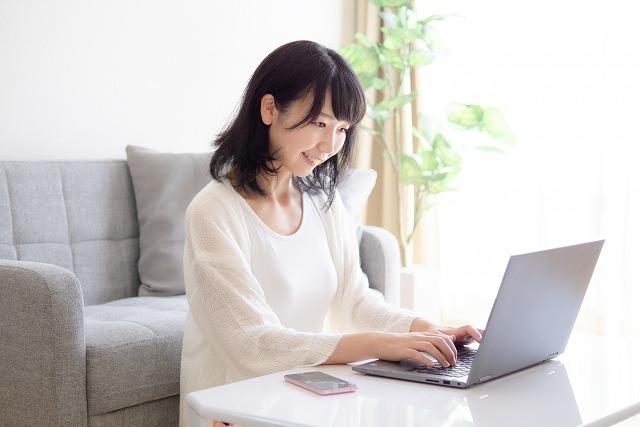 スマホとパソコンを操作する若い女性